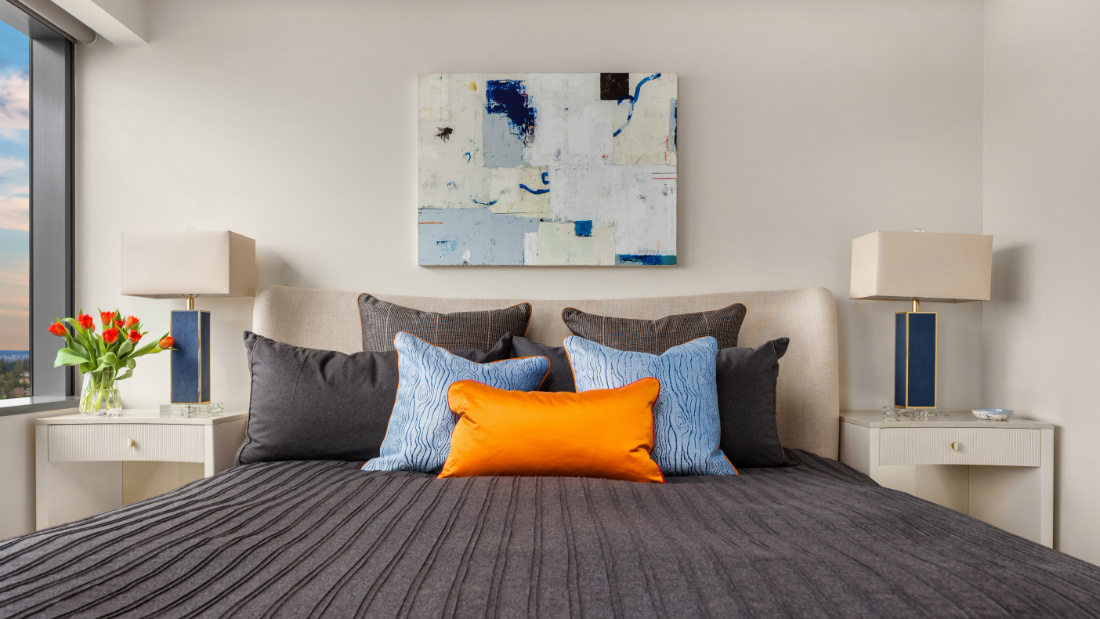bed-with-orange-throw-billow-and-gray-comforter